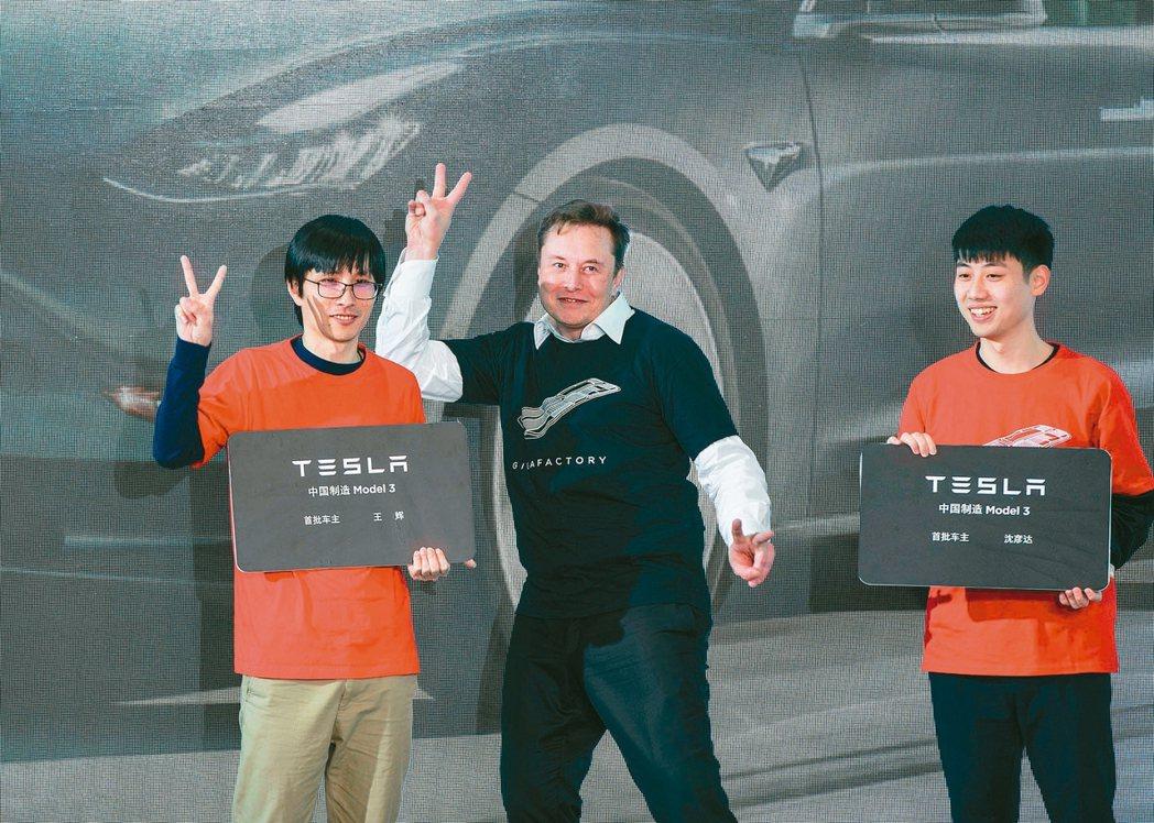 特斯拉執行長馬斯克(中)在上海工廠與首批大陸製Model 3新車主開心合照。 美...