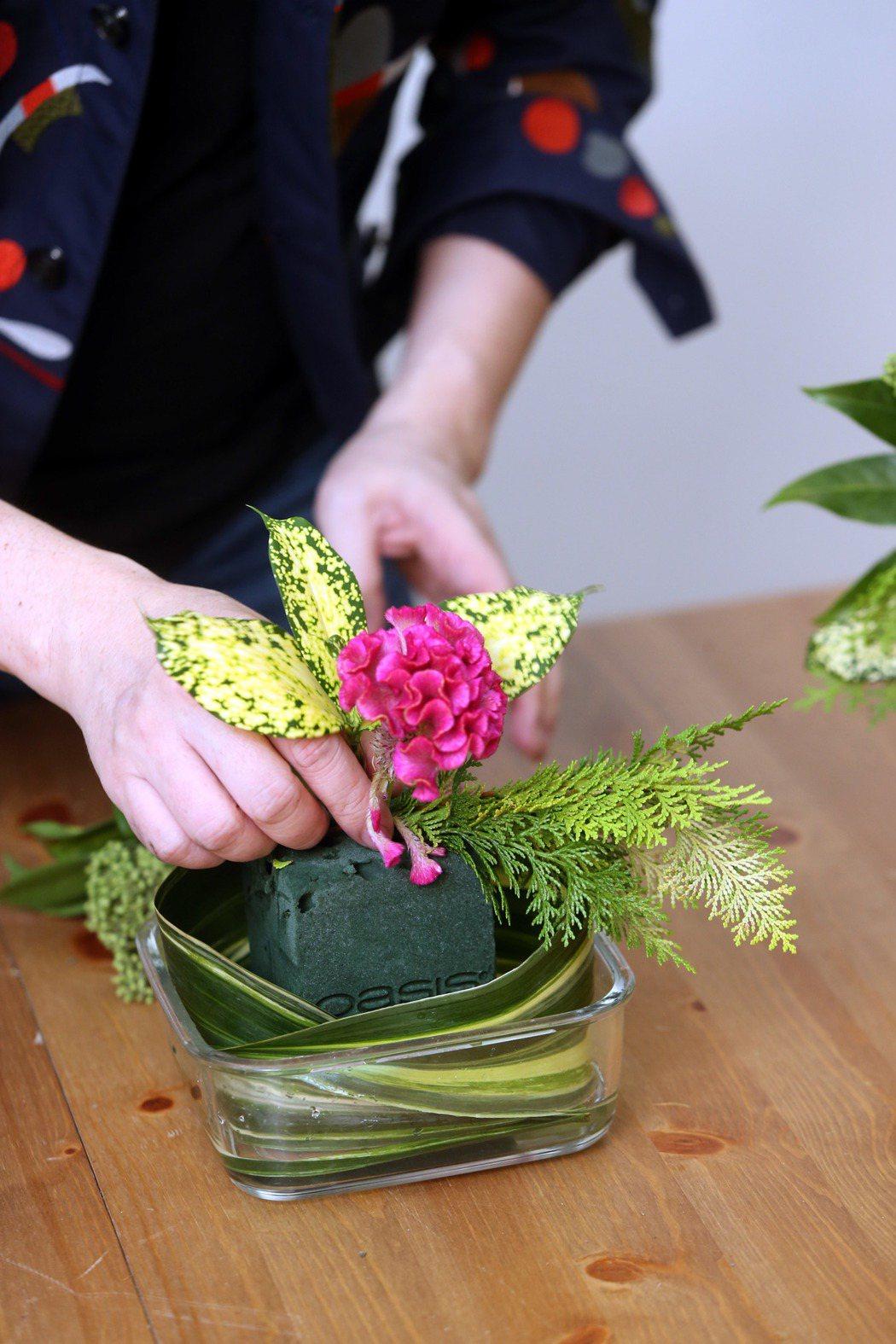 李明川用保鮮盒插花,移置花朵。記者邱德祥/攝影