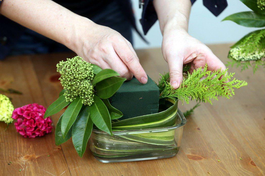 李明川用保鮮盒插花,移置枝葉。記者邱德祥/攝影