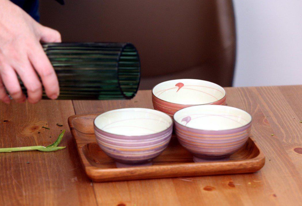 李明川用碗插花,注水。記者邱德祥/攝影