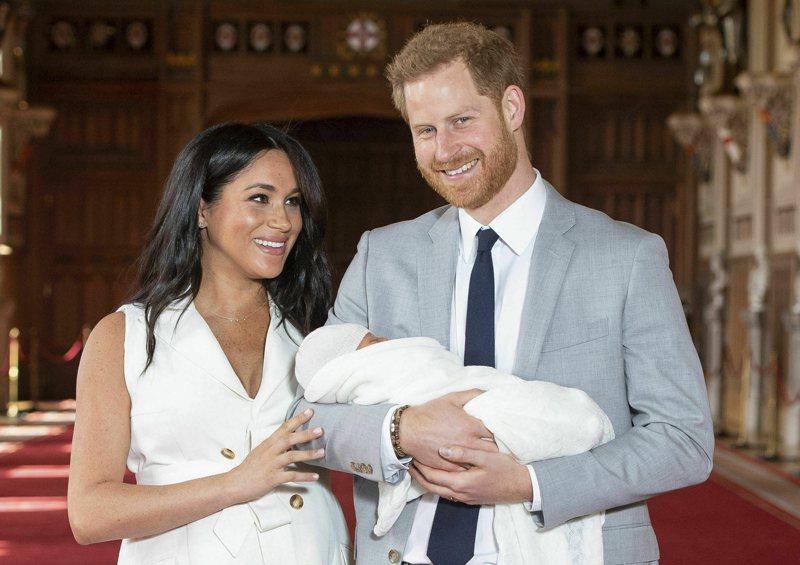 英國哈利王子(右)抱著長子亞契和夫人梅根(左)合影。美聯社
