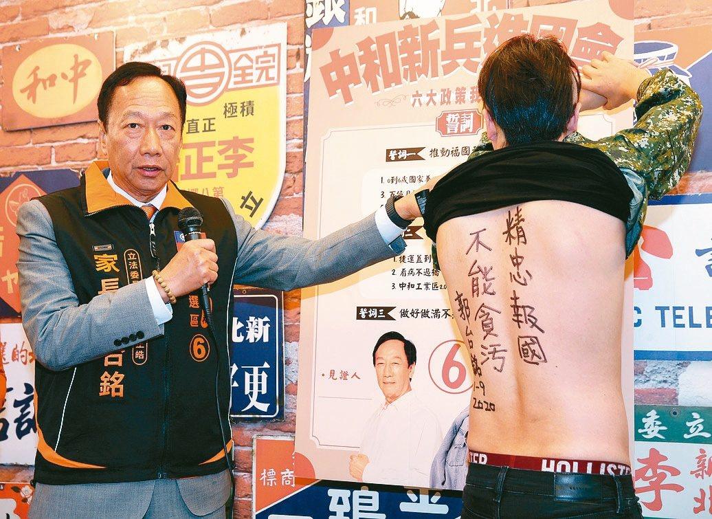 鴻海創辦人郭台銘(左)昨天化身理髮師為親民黨中和立委候選人李正皓剃髮,並在李背部...