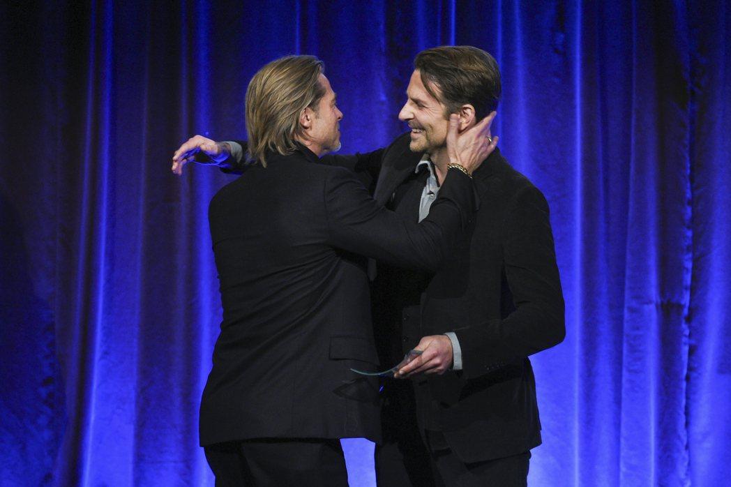 布萊德彼特(左)上台領獎,想要擁抱頒獎人布萊德利庫柏。(美聯社)