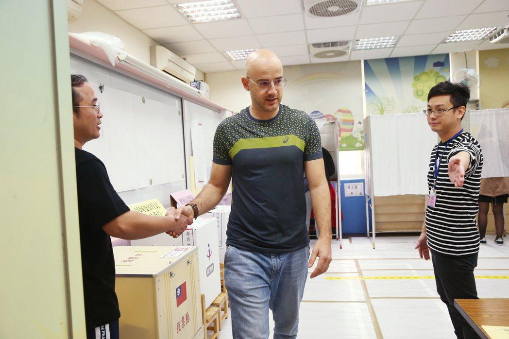 已取得台灣國籍的新住民吳鳳第一次參與總統大選投票,投票後選務人員與吳鳳握手致意,...