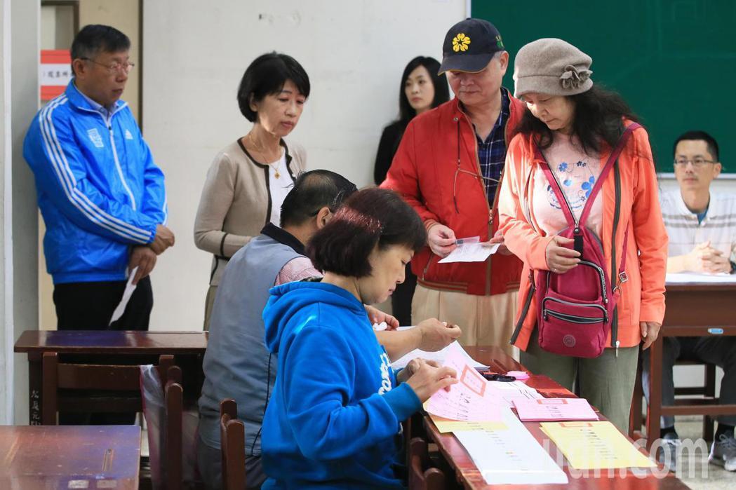 台北市長柯文哲(左)上午八點多在夫人陳佩琪(左二)陪同下排隊投票。記者潘俊宏/攝...