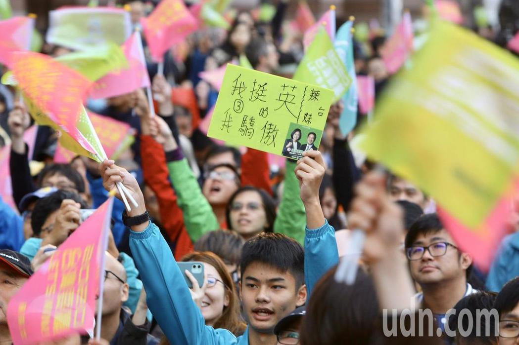 民進黨總統候選人蔡英文領先,支持者手持旗幟熱情吶喊,欣喜若狂。其中一名支持者還在...