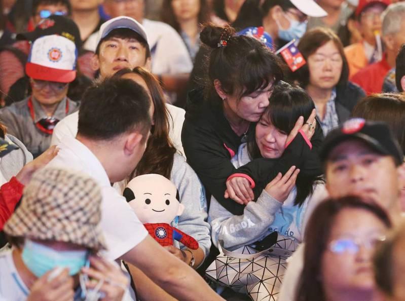 韓國瑜敗選,韓粉抱著哭泣的孩子,似乎擔心著孩子的未來。圖非文內當事人。 記者林澔一/攝影