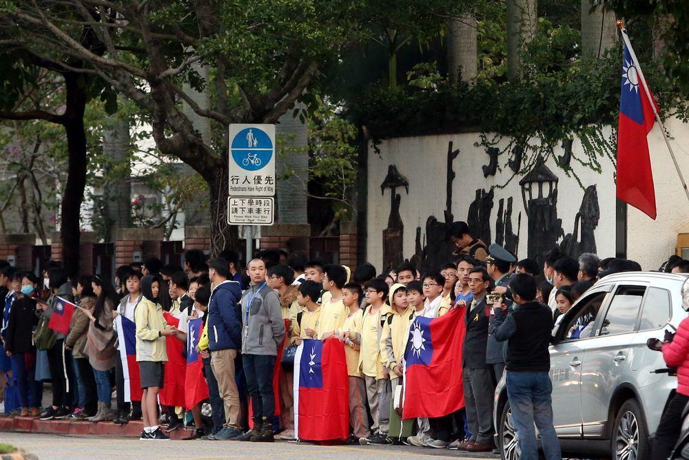 空難官兵葬禮車隊經過,沿途不少學生手持國旗在路邊致意。記者侯永全/攝影