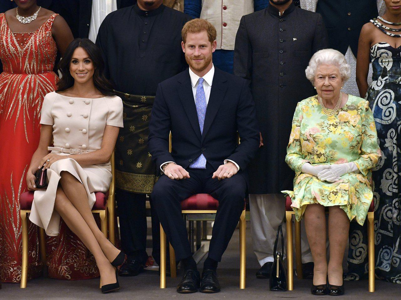 哈利(中)與梅根(左)去年6月和女王伊麗莎白二世一起出席「年輕領袖獎」頒獎典禮。...