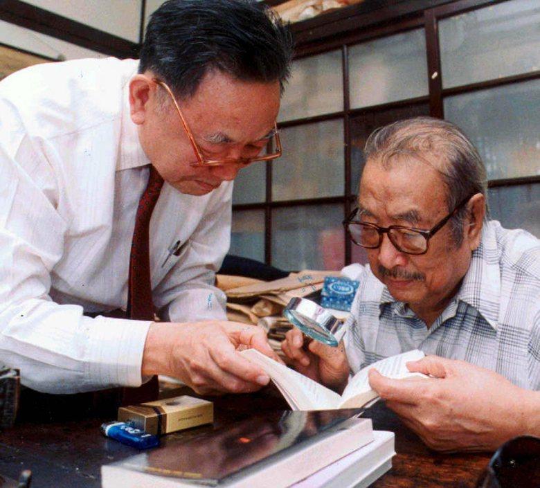臺靜農(右)以放大鏡讀梁羽生(左)著作。攝於1988年,此為溫州街18巷6號故居。 圖/聯合報系資料照