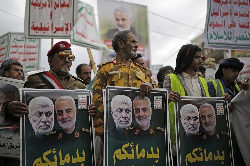 葉門胡塞軍手持兩位將領的遺照,抗議美軍的刺殺行動,攝於葉門。 圖/美聯社