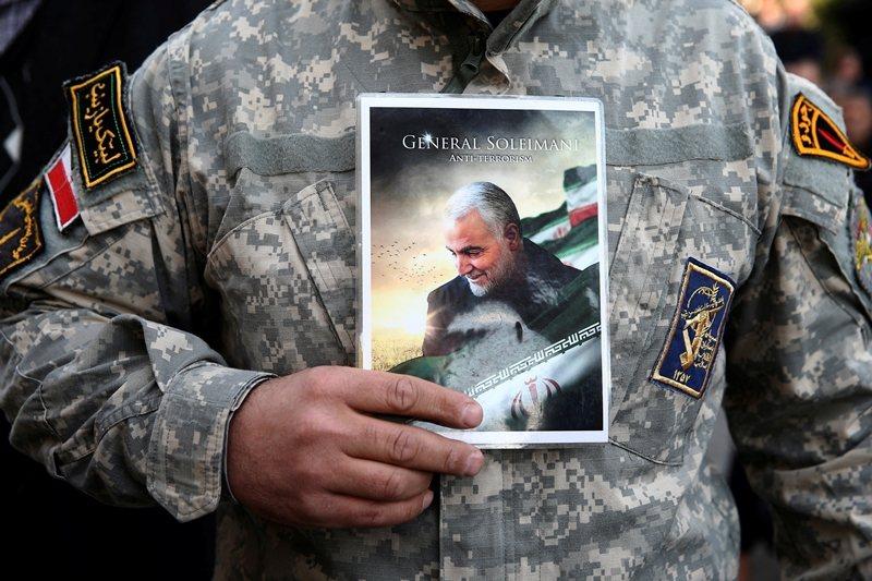 一名士兵手持伊朗革命衛隊聖城旅指揮官蘇萊曼尼的照片。 圖/路透社