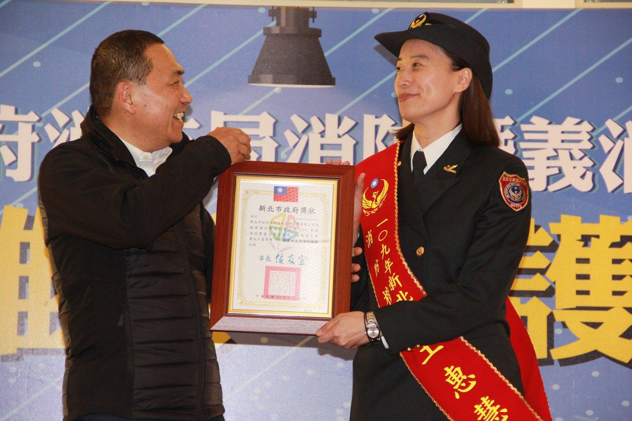 新北市消防局火場調查科專員王惠慧(右)從市長侯友宜手中接過獎狀。記者陳俊智/攝影