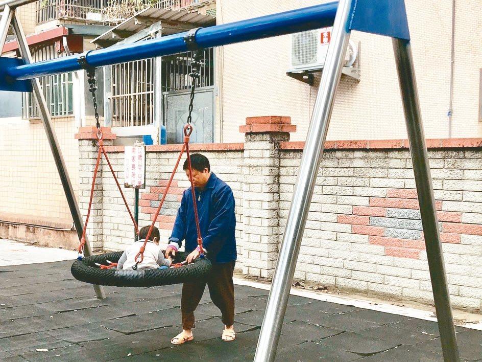 新竹縣竹北市豆子埔公園這次新設的鳥巢鞦韆,大人推著小孩玩耍,互動熱絡。 記者郭政...