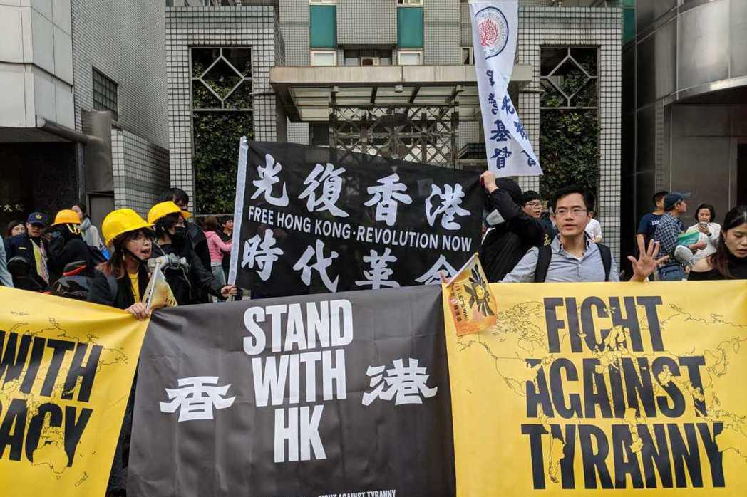 造勢活動中不時會看到香港人高舉「光復香港,時代革命」旗幟。 圖/作者自攝