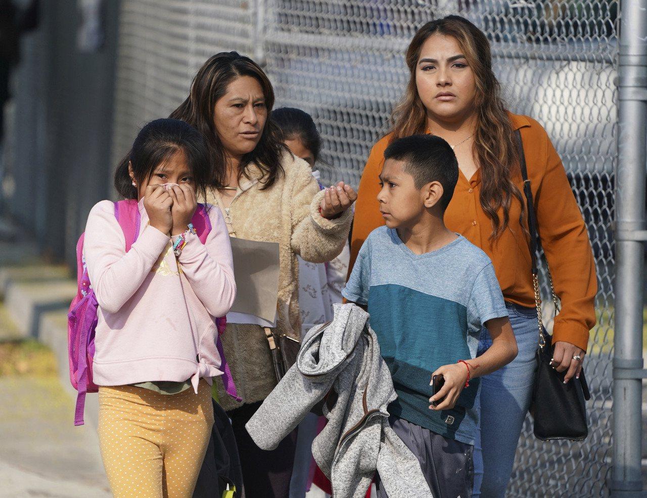 事件發生後,家長帶小孩離開學校,一名女童用衣服遮口鼻。美聯社