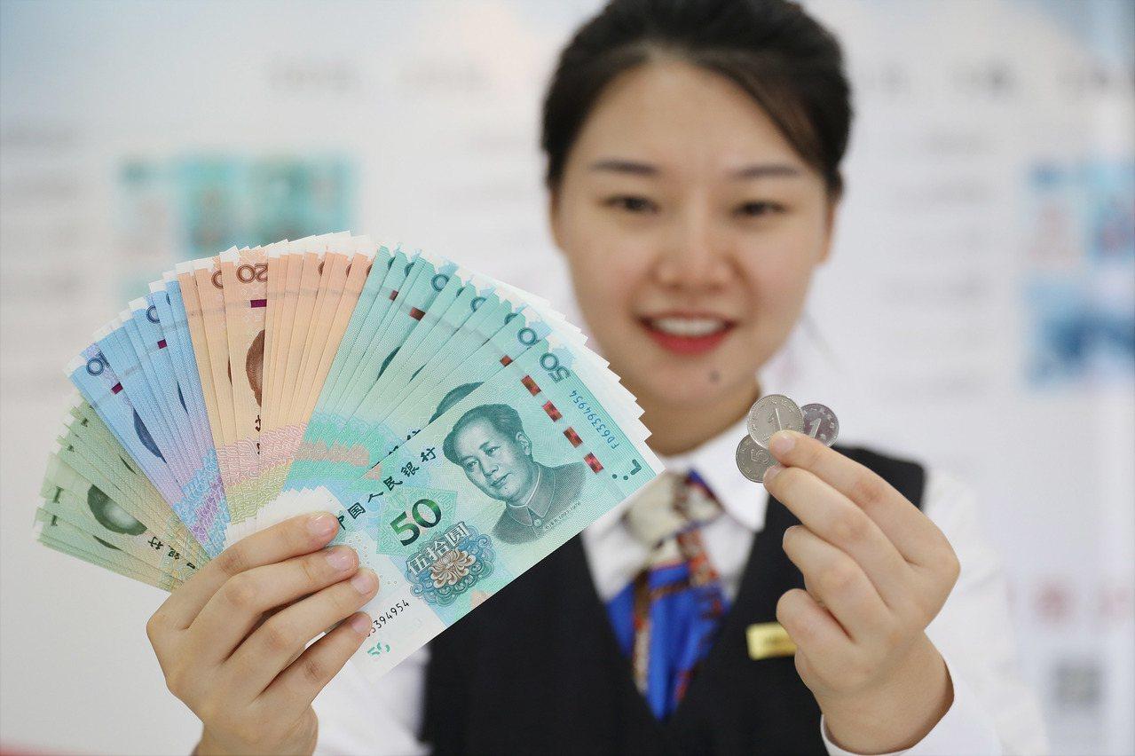 中國工商銀行行員展示2019年版第五套人民幣。(取自上海證券報)