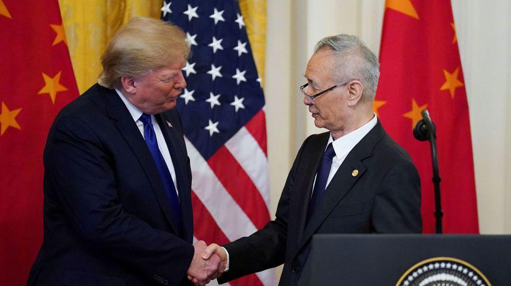 美國總統川普15日與中國副總理劉鶴(右)簽署美中第一階段貿易協議後,相互握手致意...