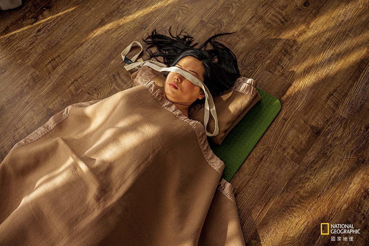 在北京悠季瑜伽學院的一間練習室裡,一名婦女正在做攤屍式大休息。悠季是中國最大的連...