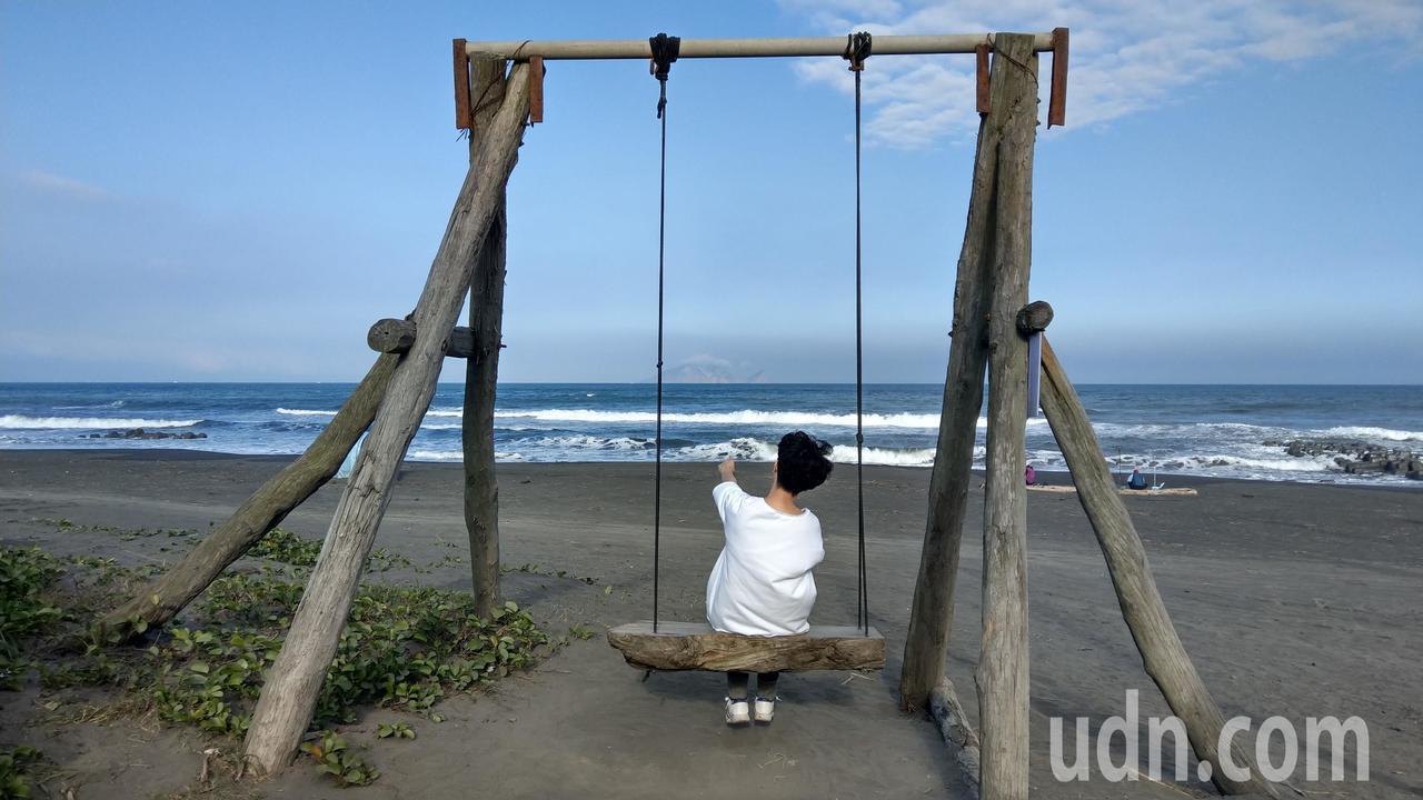 宜蘭壯圍沿海「盪鞦韆」,吸引很年多輕人喜歡來這裡捕捉海天一色的美景。記者戴永華/...