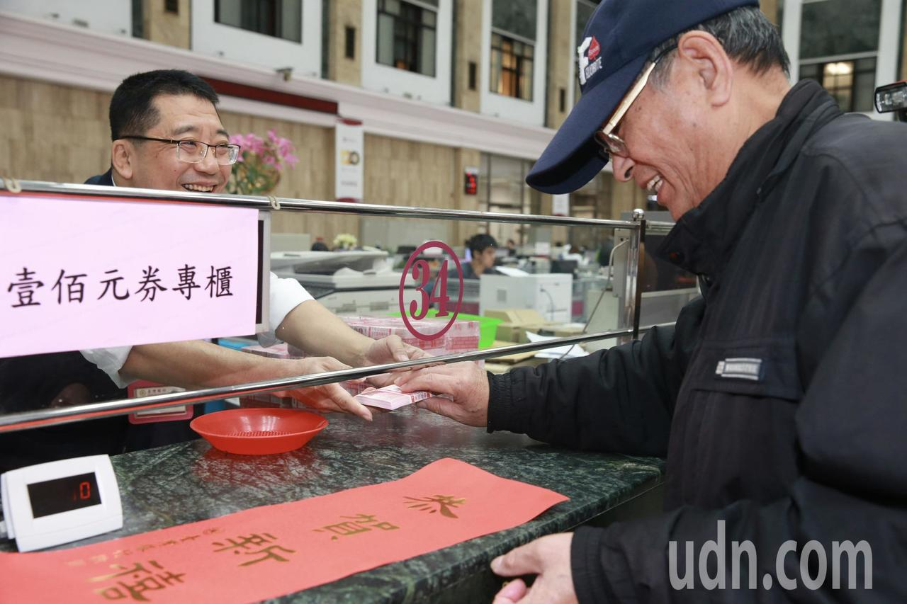 一早台灣銀行總行就有民眾在門口排隊等候換新鈔,台銀準備了成疊的紅色百元新鈔,滿足...
