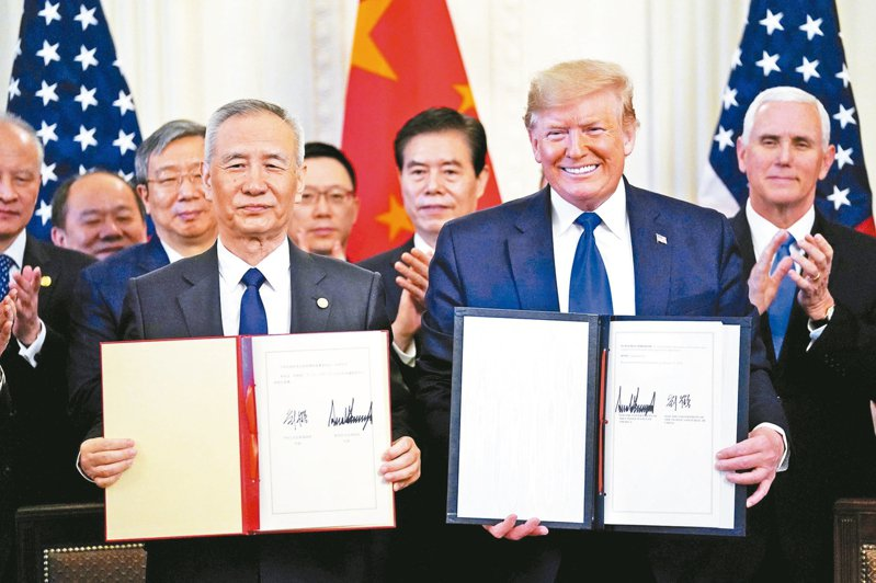 美國總統川普(前排右)和大陸副總理劉鶴(前排左)十五日在雙方官員陪同下,秀出兩人簽名的中英文版協議。 (路透)
