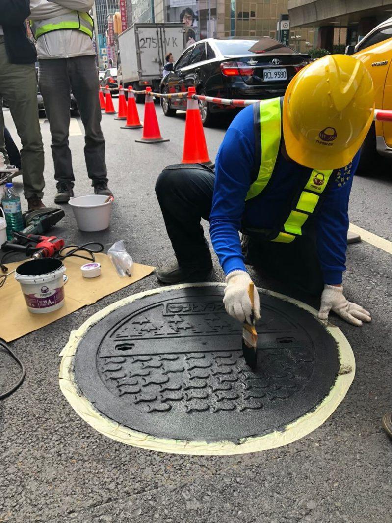 台北市訂定「台北市市區道路人孔蓋抗滑係數標準」須達到50BPN,未來3年將逐步塗佈孔蓋抗滑材料,改善不符合抗滑標準的人孔蓋。圖/北市工務局提供
