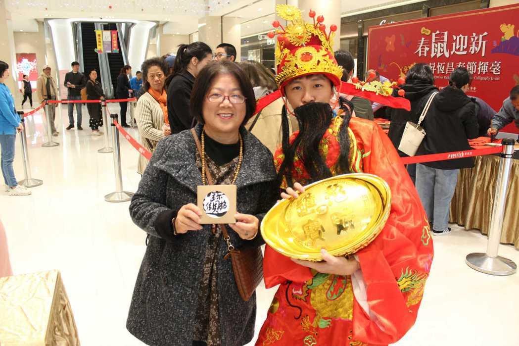 民眾搶著與財神爺合照,只要將拍照上傳臉書還能參加抽獎,最大獎為價值1980元昇恆...