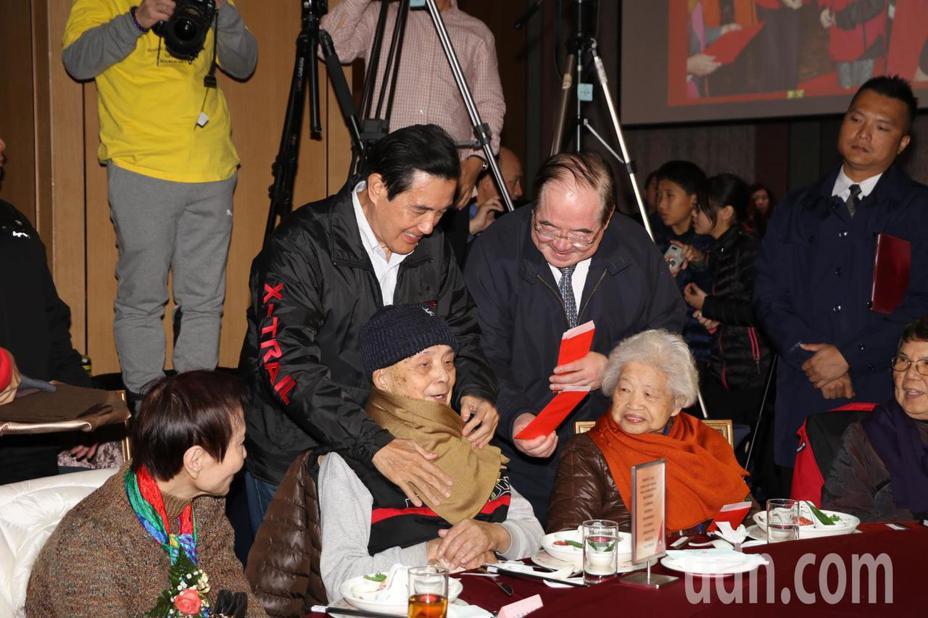 前總統馬英九為獨居長輩繫上圍巾,先嗇宮董事長李乾龍送上紅包。記者施鴻基/攝影