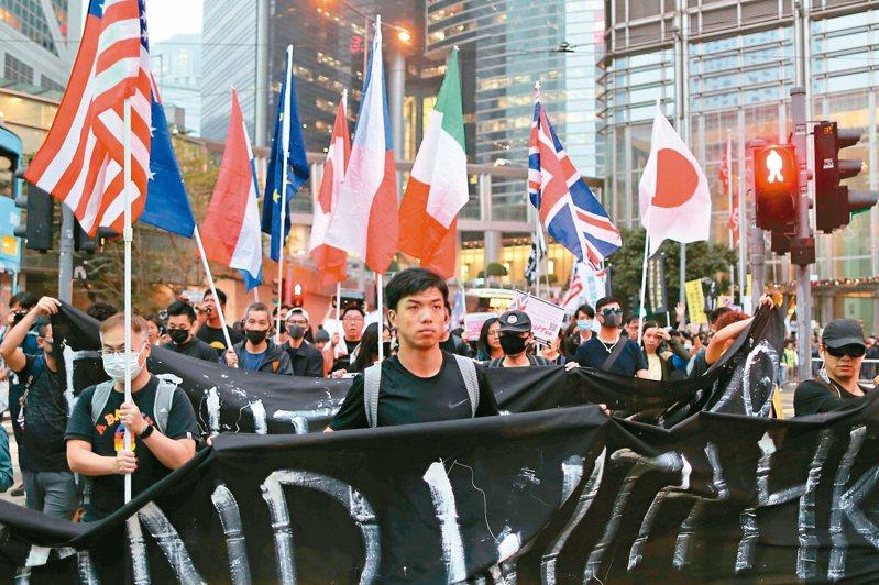 有港民發起於今日集會,呼籲國際制裁港府官員。圖為去年十二月十九日香港示威者拿著各國國旗遊行,求國際支持。 路透