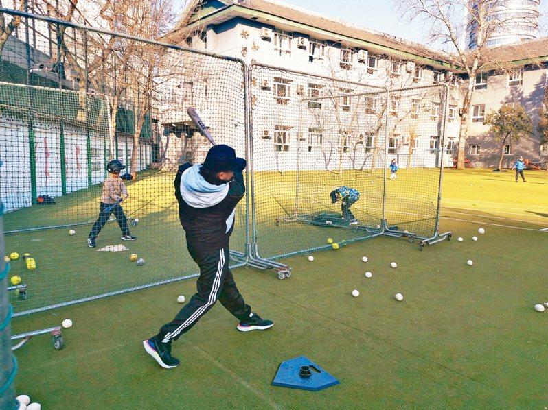 連庭瑋大學畢業後加入北京同啟新星棒壘球俱樂部,成為青少年棒球教練。圖為連庭瑋向小隊員示範動作。 (中新社)