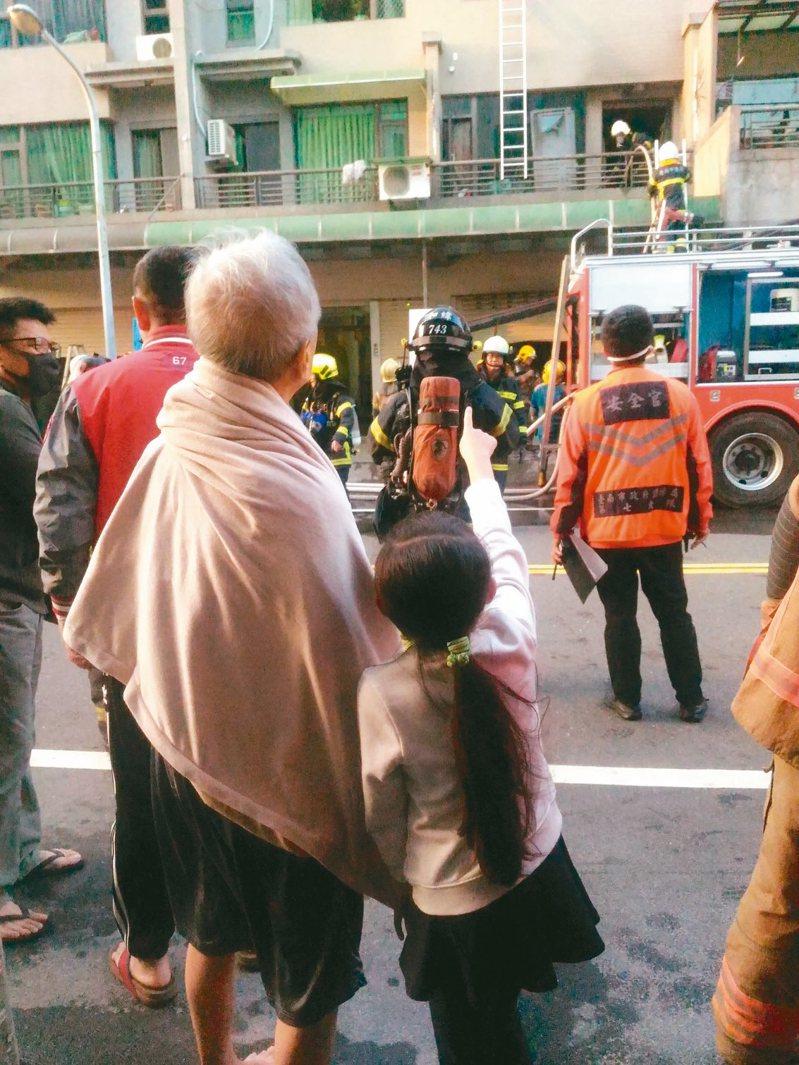 九歲張姓女童架梯協助自己和祖父、弟弟從火場脫困;事後爺孫相依站在路旁看消防人員搶救。 記者黃宣翰/攝影