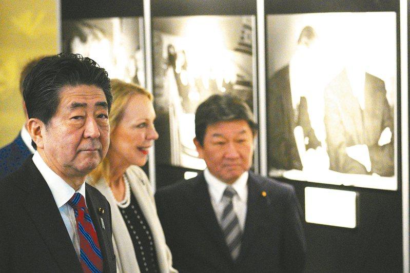 日相安倍晉三(左)與美國故總統艾森豪的孫女瑪麗(中),十九日在東京美日安保條約修訂六十周年紀念活動上,參觀一場照片展。 (法新社)