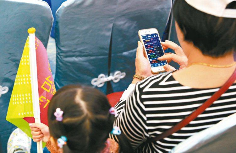 今年電子交易比重將突破七成,智慧手機早已成為下單、看盤工具。 圖/聯合報系資料照...