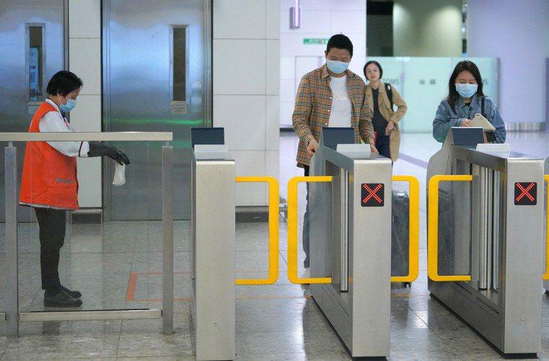 20日凌晨公布,武漢肺炎統計死亡病例3宗。圖為北京西始發、途徑武漢的G79高鐵列車抵達香港西九龍站,許多旅客戴著口罩出站,車站工作人員及時給出站閘機消毒。 香港中通社圖片