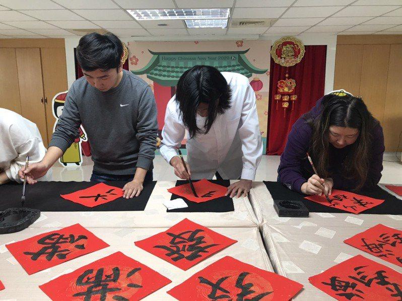 來自蒙古的大學生,揮筆寫春聯,向認養人拜年。圖/家扶基金會提供