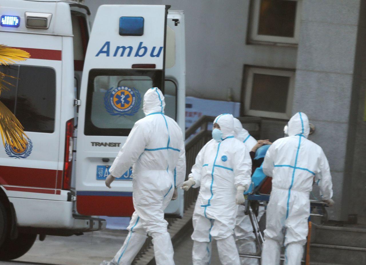 武漢肺炎確診病例短短兩天暴增,圖為武漢醫護人員移送病患到醫院。 歐新社