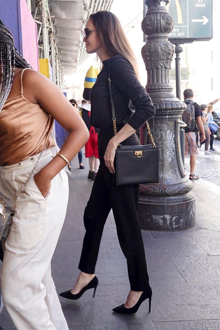 好萊塢女星安潔莉娜裘莉肩背Trifolio黑色牛皮包並搭配Judy黑色麂皮高跟鞋...
