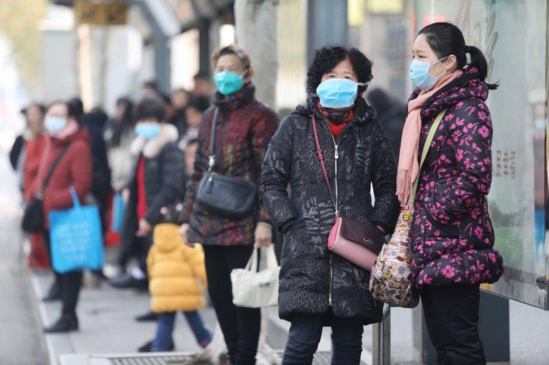 武漢肺炎疫情擴大,當地民眾戴口罩自保。(圖/歐新社)