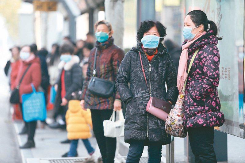 武漢肺炎確診病例暴增,在疫情發源地武漢華南海鮮市場附近等公車民眾,廿日紛紛戴上口罩。歐新社