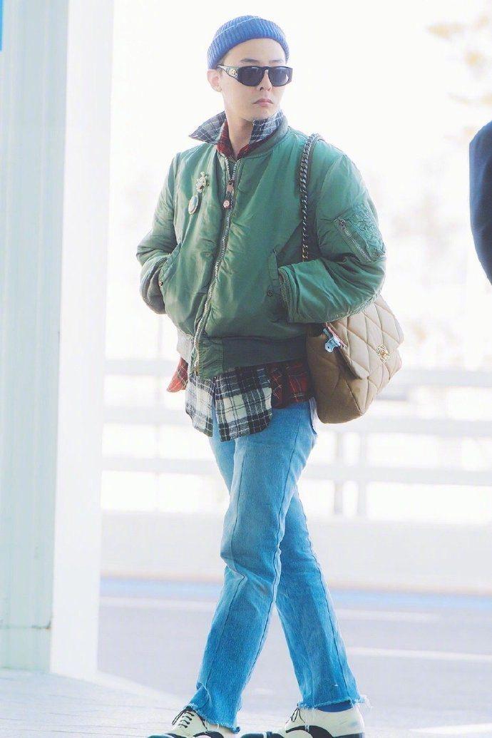 GD日前出發巴黎的機場時尚用軍綠色的外套配格紋襯衫、牛仔褲再搭上黑白德比鞋,背著...