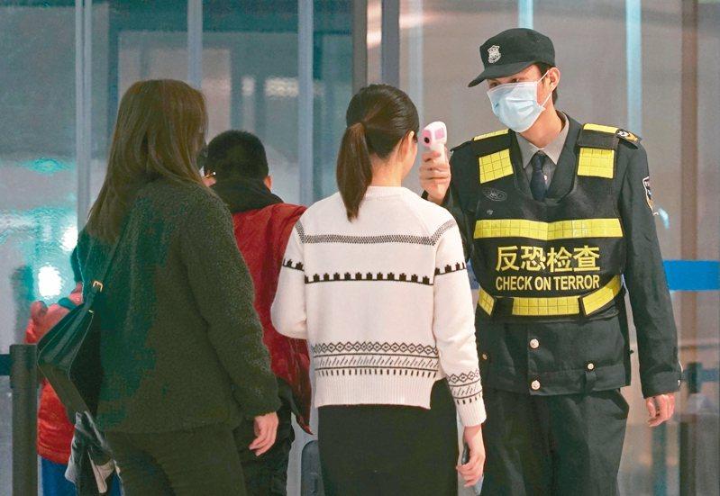 新型冠狀病毒肺炎疫情擴散,重災區湖北武漢已加強管控人員進出。圖為武漢天河機場工作人員為旅客量體溫。 (美聯社)