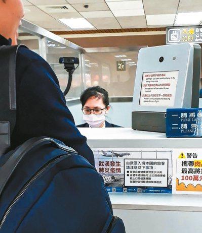武漢肺炎疫情擴散,松山機場的入境旅客紛紛戴上口罩自我照護,入境處也豎立防疫標示牌...