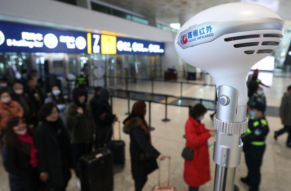 圖為武漢天河機場,工作人員對旅客進行體溫檢測。新華社