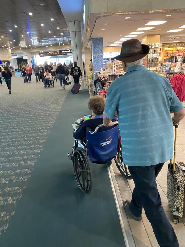 登機前,丈夫拄著拐杖緩緩推著輪椅帶妻子抓寶,並幫她加油打氣/圖片截自reddit...