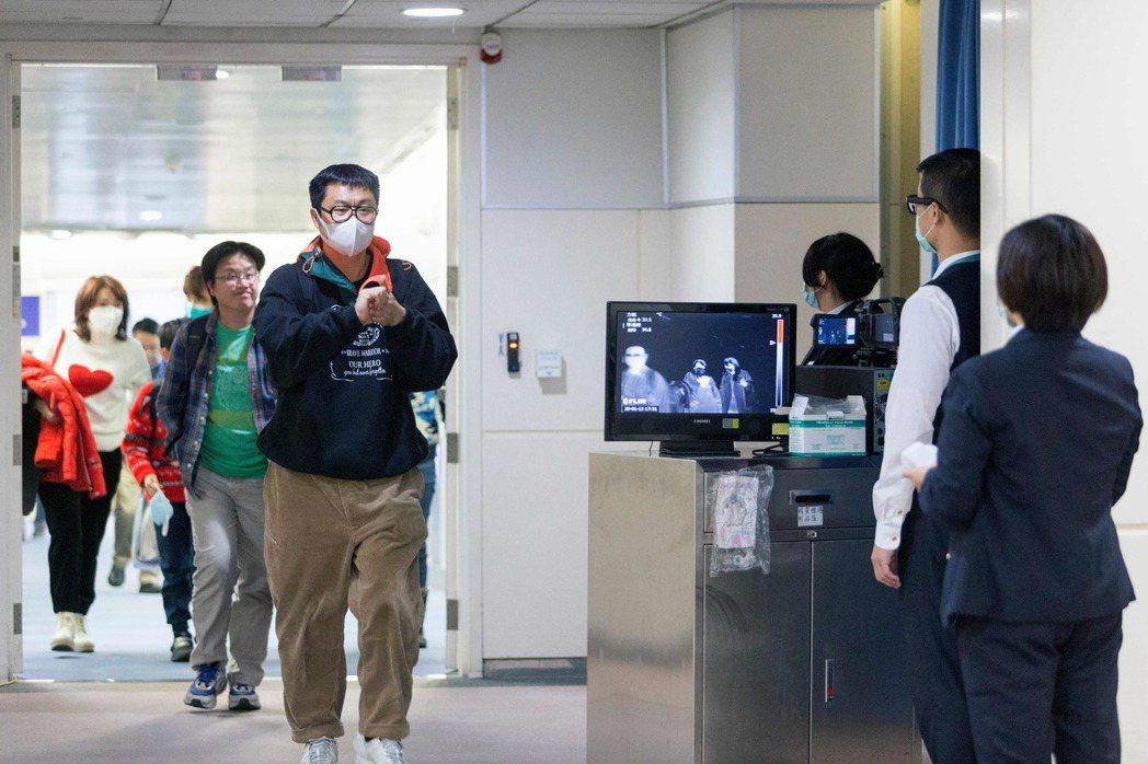 台灣出現1例武漢肺炎確診病例。圖為台灣疾管局人員在機場監測從武漢抵達的班機乘客。...