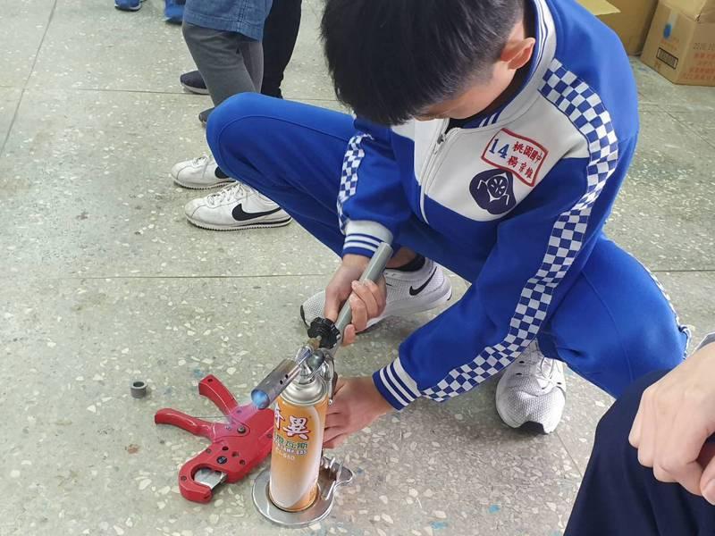 「水電維修體驗」讓學生了解水電工作自來水配管,向學生介紹如何使用噴燈,將PVC水管做成擴管、喇叭管等技術。記者陳夢茹/攝影