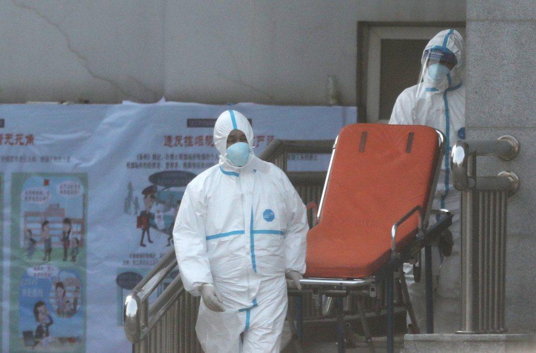 圖為武漢醫護人員身著防護服轉移確診患者以集中隔離治療。(歐新社)