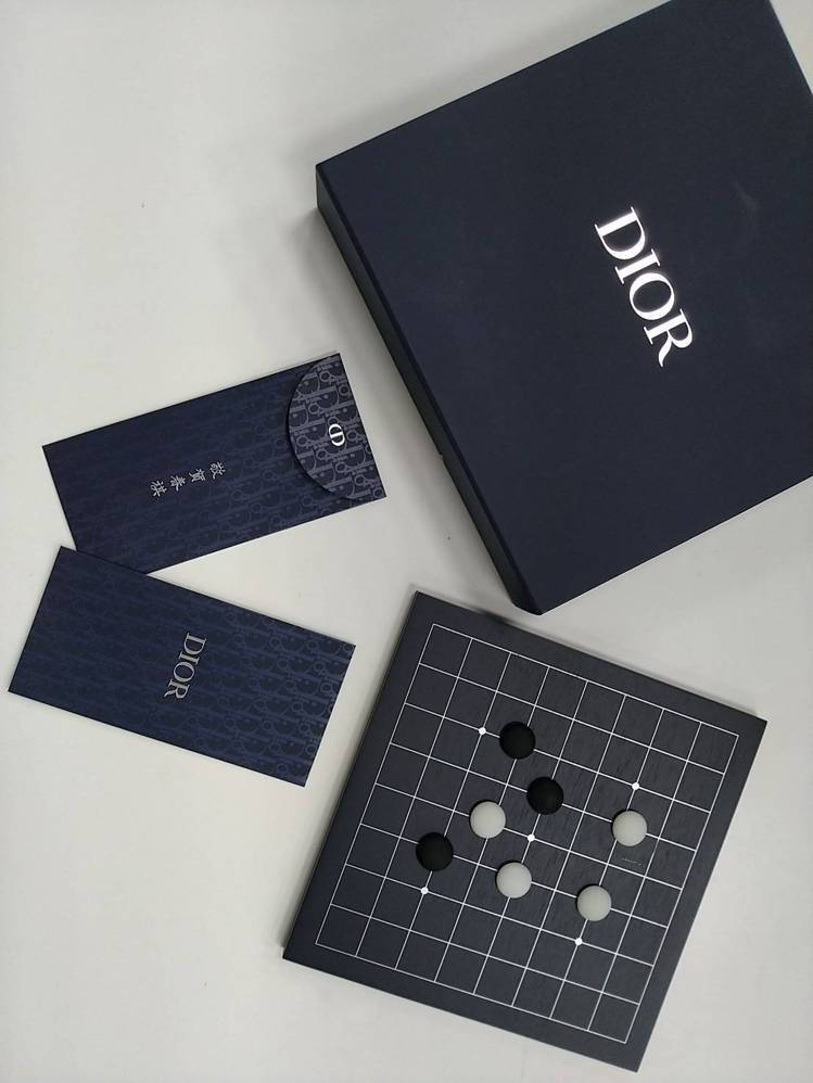 DIOR以經典海軍藍和Oblique印花打字紅包袋,並附上典雅的棋盤盒,讓年節多...