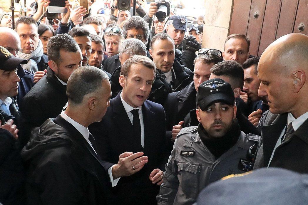 法國總統馬克宏22日赴耶路撒冷舊城區,正準備參訪聖亞納教堂時,被拍到當場訓斥意圖...
